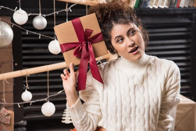 멀리보고 활과 선물 상자를 들고 젊은 여자