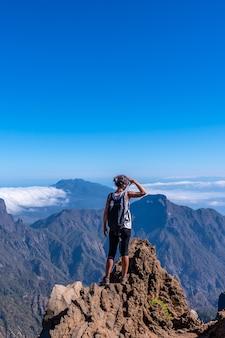 Молодая женщина смотрит с вершины вулкана кальдера-де-табуриенте возле роке-де-лос-мучачос одним летним днем, ла-пальма, канарские острова. испания