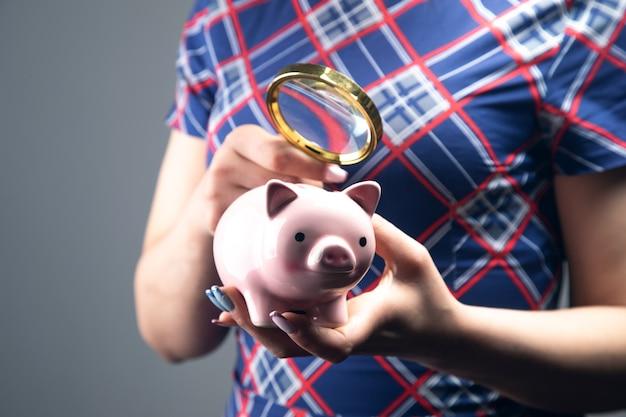 젊은 여자는 돋보기와 함께 돼지 저금통을 살펴 봅니다. 축적 된 자금 연구의 개념