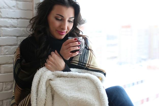 Молодая женщина смотрит в окно новой квартиры