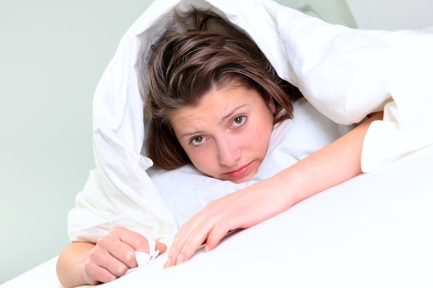 熱でベッドに横たわっている若い女性