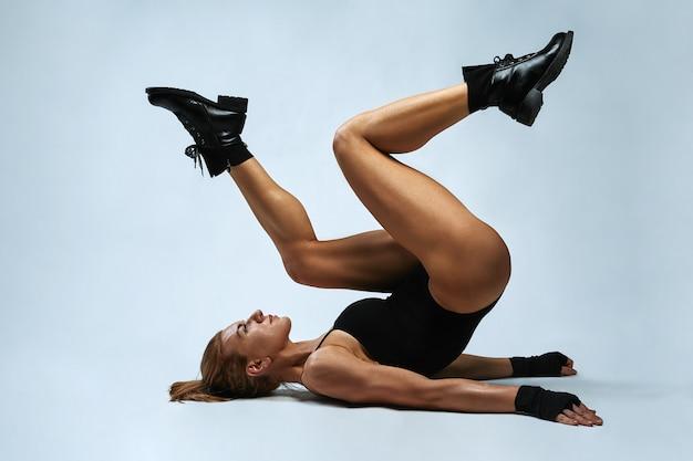 白い背景の上の彼女の大きな長い脚と底を示すスタジオの床に横たわっている若い女性