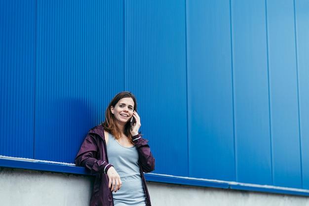Молодая женщина делает мобильный звонок в спортивной одежде