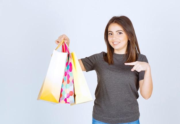 買い物袋を持って指さしている若い女性モデル。