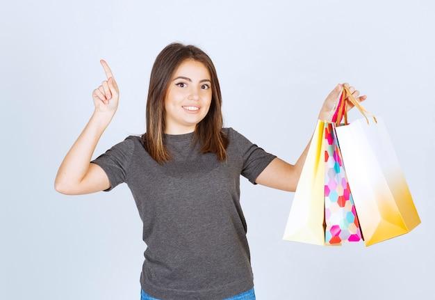 그녀의 쇼핑 가방을 들고 가리키는 젊은 여자 모델.