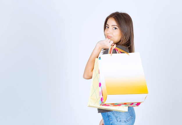 흰색 배경에 쇼핑백을 많이 들고 젊은 여자 모델. 고품질 사진