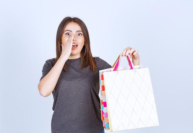 흰색 배경에 쇼핑백을 많이 들고 젊은 여자 모델.