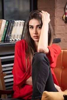 앉아서 포즈를 취하는 빨간 블라우스에 젊은 여자 모델.
