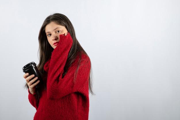 一杯のコーヒーを保持している赤いセーターの若い女性モデル