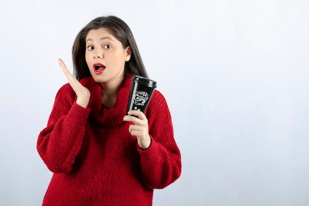 커피 한 잔을 들고 빨간 스웨터에 젊은 여자 모델