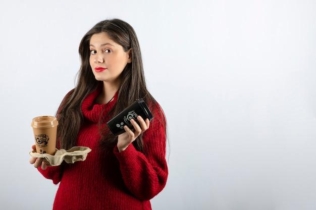 커피 두 잔을 들고 빨간 스웨터에 젊은 여자 모델