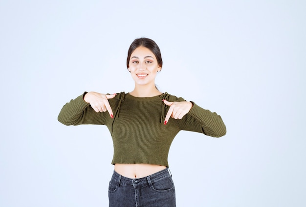 Модель молодой женщины стоя и указывая пальцами вниз.
