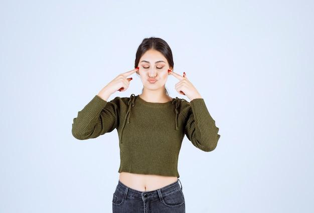 目を閉じて立ち、頬を指差す若い女性モデル。