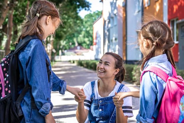 若い女性は、手をつないでいる娘たちを道徳的にサポートし、子供たちを励まし、生徒たちを学校に連れて行きます。