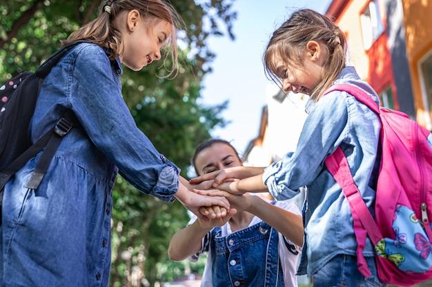 若い女性は、手をつないでいる娘たちを道徳的にサポートし、子供たちを励まし、母親は生徒たちを学校に連れて行きます。
