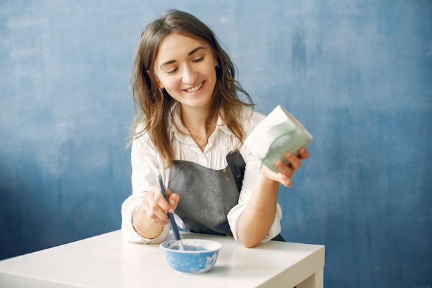 Молодая женщина красит посуду в глиняной посуде