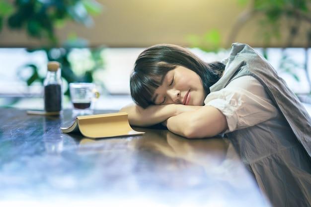 本とコーヒーを片手に適度に明るい部屋で昼寝をしている若い女性