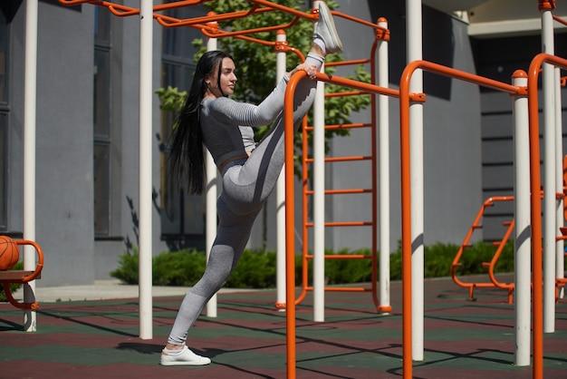 운동 체격의 젊은 여성이 스포츠 분야의 수평 막대에 다리 근육을 뻗어 신선한 공기를 훈련하면서