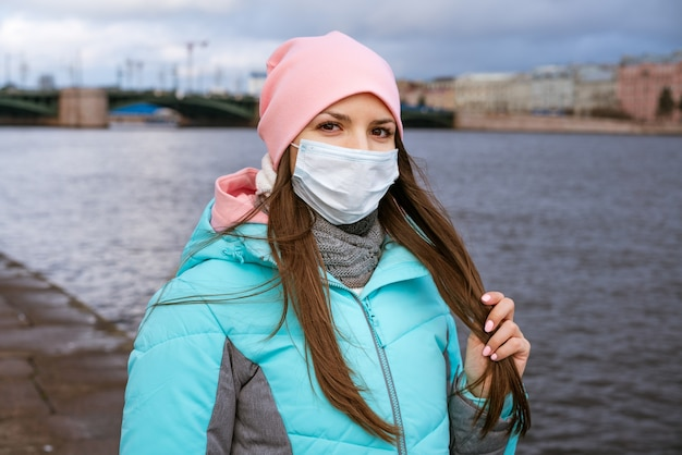 暖かい服と医療用マスクを身に着けた白人民族の若い女性が堤防に沿って歩きます...