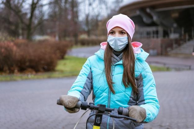 暖かい服と保護マスクを身に着けた白人民族の若い女性が、スクーターに乗って...