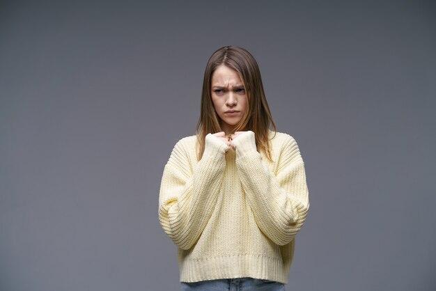 회색 배경에 노란색 스웨터를 입고 매우 화가 난 백인 민족의 젊은 여성이 그녀의 손을 잡고 있습니다.