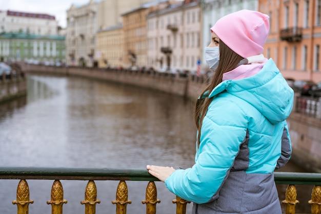 白人民族の若い女性が暖かい上着とプロテクトを着て川沿いを歩く