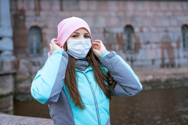 白人民族の若い女性が、暖かい上着と保護具を身に着けて川沿いの街を歩いています...