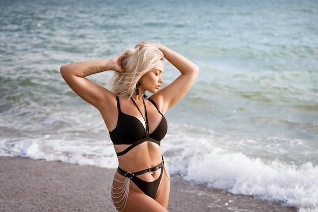 晴れた夏の日に、黒い水着を着たヨーロッパ人の若い女性が海岸に立っています。