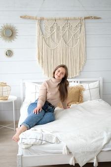 Молодая женщина европейской внешности сидит на кровати в своей уютной спальне с улыбкой на лице