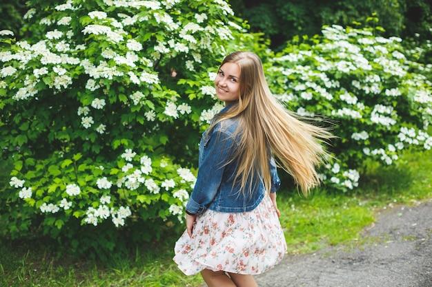 短いドレスを着た長いブロンドの髪を持つヨーロッパの外観の若い女性は、白い花の茂みの背景に立っています。晴れた春の日。自然な女性の美しさ