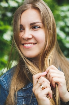 짧은 드레스를 입은 긴 금발 머리에 유럽풍의 젊은 여성이 흰 꽃이 만발한 덤불을 배경으로 서 있습니다. 화창한 봄날. 자연스러운 여성미