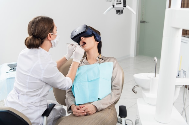現代の歯科治療を受けている若い女性。vrメガネを使用して、不快な歯科治療から気をそらしています。