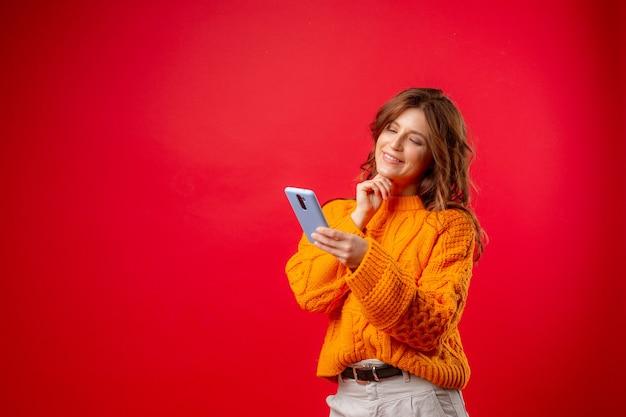 赤の若い女性がメッセージを入力して携帯電話を持っています