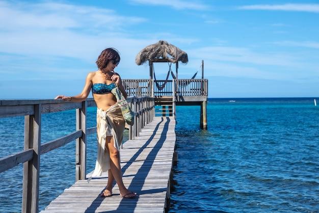 ロアタン島のカリブ海の上の木製の通路の若い女性。ホンジュラス
