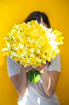 背景が黄色の若い女性は、黄色い水仙の花束で顔を覆っています。女性の日のコンセプトです。