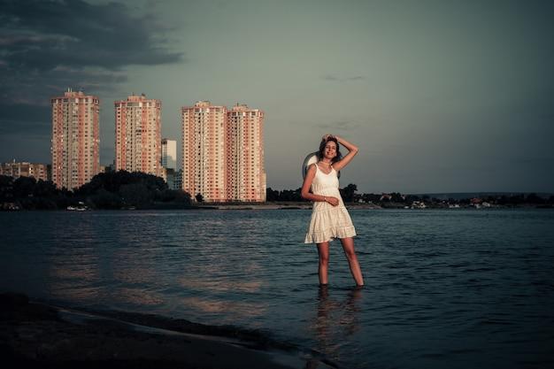 Молодая женщина на фоне многоэтажных домов красивая счастливая блондинка в белом летнем платье ...