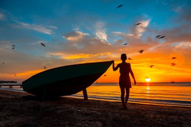 ロアタン島、ウエストエンドサンセットのボートに乗ってビーチで若い女性。ホンジュラス