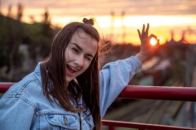 아름 다운 석양에 포즈 다리에 젊은 여자.