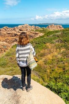 フランス、ブルターニュのコートダモール、ペロスギレックの町、プルマナッコ港の灯台ミーンルスの隣の海岸にいる若い女性。
