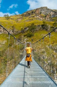 ラローのホルツァルテ吊橋の若い女性。スペインのナバラとピレネーアトランティックの北にあるイラティの森またはジャングルで