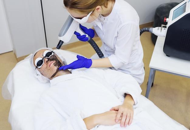 Молодая женщина на процедуре углеродного пилинга на поверхности современной косметологической комнаты. лазерная косметология
