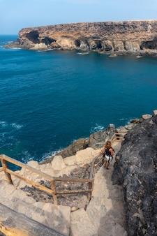 Молодая женщина на лестнице тропы к пещерам аджуй, пахара, западное побережье острова фуэртевентура, канарские острова. испания