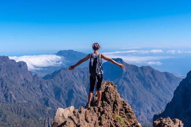 Молодая женщина на вершине вулкана кальдера-де-табуриенте недалеко от роке-де-лос-мучачос одним летним днем с распростертыми объятиями, ла-пальма, канарские острова. испания