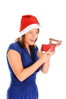 흰색 배경 위에 크리스마스 선물을 여는 젊은 여자