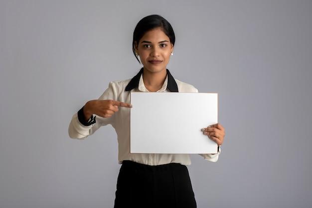 Молодая женщина или предприниматель, держа в руках вывеску на сером фоне.