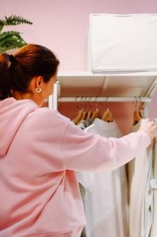 한 젊은 여성이 옷장에 옷을 정리합니다. 옷장에 있는 물건을 보고 무엇을 입을지 선택합니다. 집에서 청소하고 정리하는 사람들