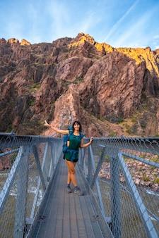Молодая женщина над рекой колорадо на мосту на тропе брайт энджел в гранд-каньоне. аризона