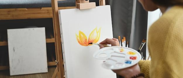 若い女性の画家が彼女のワークショップでポスターカラーで絵を描いています