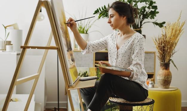 Молодая женщина рисует в своей квартире масляными красками. студентка рисует в художественной студии. концепция исследования изящного искусства.