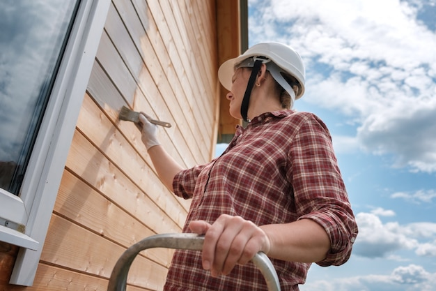 젊은 여성이 새 목조 주택의 외부 벽을 그립니다. 시골집을 그리는 과정